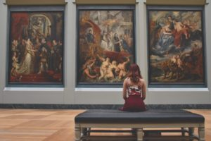 a woman sitting on a bench in front of large works of art in an Italian art gallery