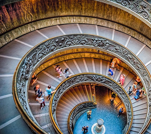 people-walking-on-spiral-staircase-in-roman-museum